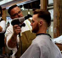 Gustavus AK barber blow drying client's hair